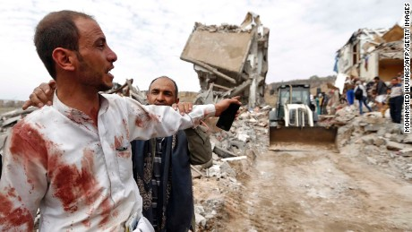 A Yemeni man covered in blood reacts as people search for survivors following Friday's strike.