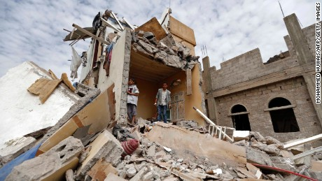 Yemenis stand in the rubble of a house destroyed Friday in an airstrike in Sanaa.