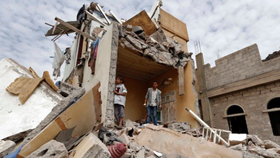 Yemenis stand in the rubble of a house destroyedin an air strike in the residential southern Faj Attan district of the capital, Sanaa, on August 25, 2017.The attack destroyed two buildings in the southern district, leaving people buried under debris, witnesses and medics said. / AFP PHOTO / Mohammed HUWAIS        (Photo credit should read MOHAMMED HUWAIS/AFP/Getty Images)