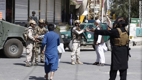 Afghan security officials take positions Friday near the Kabul mosque after the attack.