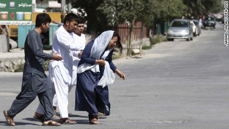 Afghans flee the site of an attack on a Shiite Muslim mosque in Kabul during Friday prayers.