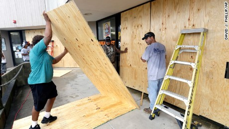 Christopher Beafneaux, left, Ernesto Villarreal, center, and Roman Lopez board up windows of a business in Galveston.