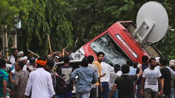 Dera Sacha Sauda sect members overturn an OB van on the streets of Panchkula, India, Friday, Aug. 25, 2017.