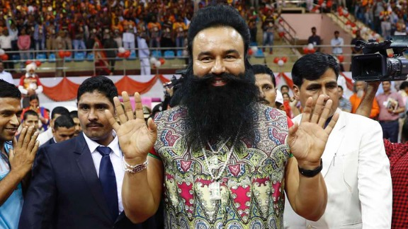 "FILE- In this Oct. 5, 2016 file photo, Indian spiritual guru who calls himself Saint Dr. Gurmeet Ram Rahim Singh Ji Insan, center, greets followers as he arrives for a press conference ahead of the release of his new movie ""MSG, The Warrior Lion Heart,"" in New Delhi, India. Several cities in north India were under a security lock down Thursday ahead of a verdict in a rape trial involving a controversial and hugely popular spiritual leader. (AP Photo/Tsering Topgyal, File)"