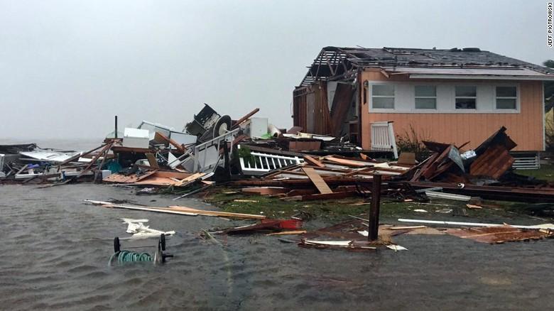 A damaged home sits amid a flood on Saturday after Hurricane Harvey slammed  Rockport, Texas
