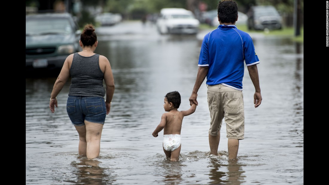 People walk through flooded streets in Galveston on August 26.