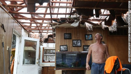 Aaron Tobias stands in what is left of his home in Rockport on Saturday. Tobias said he and his family lost everything in the storm.