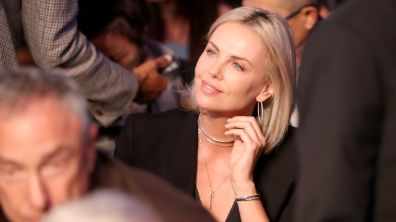 Actress Charlize Theron sits close to ringside.