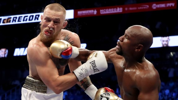 (R-L) Floyd Mayweather Jr. throws a punch at Conor McGregor during their super welterweight boxing match on August 26, 2017.