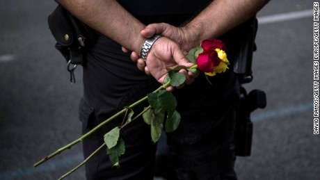 A police officer holds roses during the demonstration.