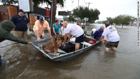 Neighbors use their personal boats to rescue flooded residents in Friendswood, Texas, on Sunday.