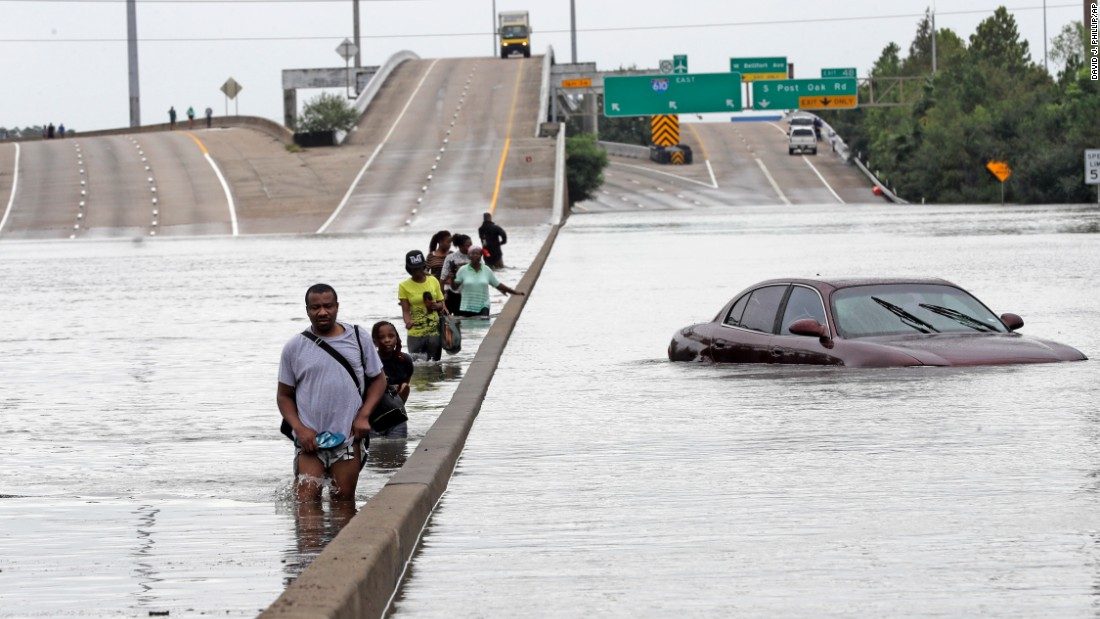 Evacuees wade through a flooded section of Interstate 610 in Houston on August 27.
