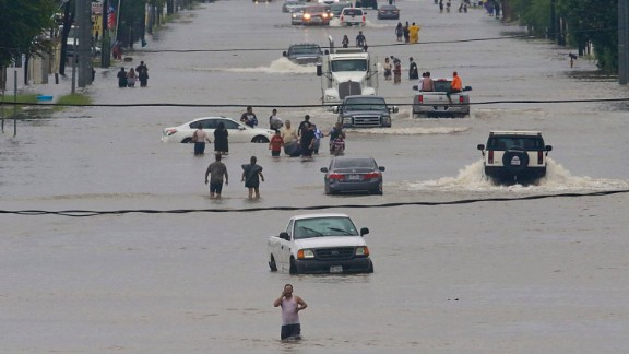 People walk through the flooded streets of Houston on August 27, 2017, after Hurricane Harvey dumped record rains.