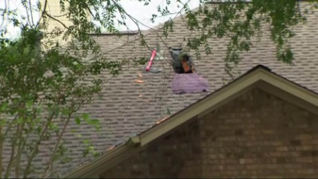 An evacuated Houston house shows where its residents broke through from the attic to escape.