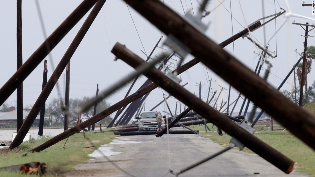 A driver works his way through a maze of fallen utility poles in Taft, Texas, on Saturday, August 26.