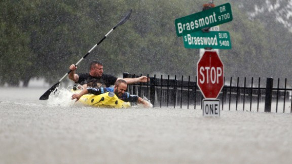 Two men try to beat the current pushing them down an overflowing Brays Bayou in Houston on August 27.