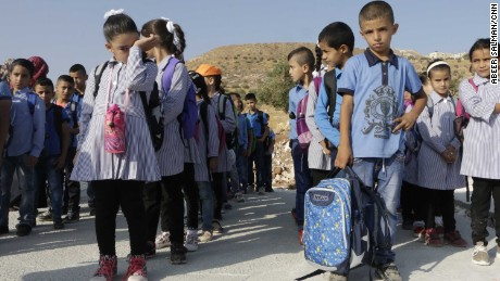 Children, including Jana Zawahra (front left), stand in line near the remains of their school east of Bethlehem.