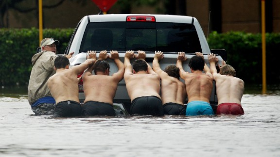People push a stalled pickup through a flooded street in Houston.