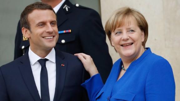German Chancellor Angela Merkel (R) and French President Emmanuel Macron leave the Elysee Palace in Paris on July 13, 2017, after an annual Franco-German Summit.  / AFP PHOTO / Patrick KOVARIK        (Photo credit should read PATRICK KOVARIK/AFP/Getty Images)