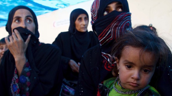 Displaced Iraqi women and children sit on the ground on the outskirts of Tal Afar on Saturday.