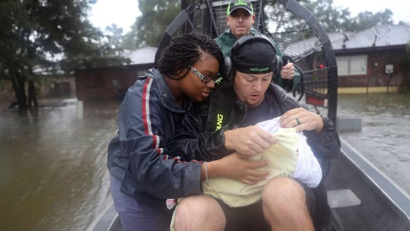 Shardea Harrison looks at her 3 week old baby Sarai Harrison being held by Dean Mize as he and Jason Legnon used his airboat to rescue them from their home in Houston on August 28.