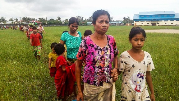 Women and children fleeing violence in their villages arrive at the Yathae Taung township in Rakhine State in Myanmar on August 26, 2017. Terrified civilians tried to flee remote villages in Myanmar's northern Rakhine State for Bangladesh on August 26 afternoon, as clashes which have killed scores continued between suspected Rohingya militants and Myanmar security forces. / AFP PHOTO / Wai Moe        (Photo credit should read WAI MOE/AFP/Getty Images)