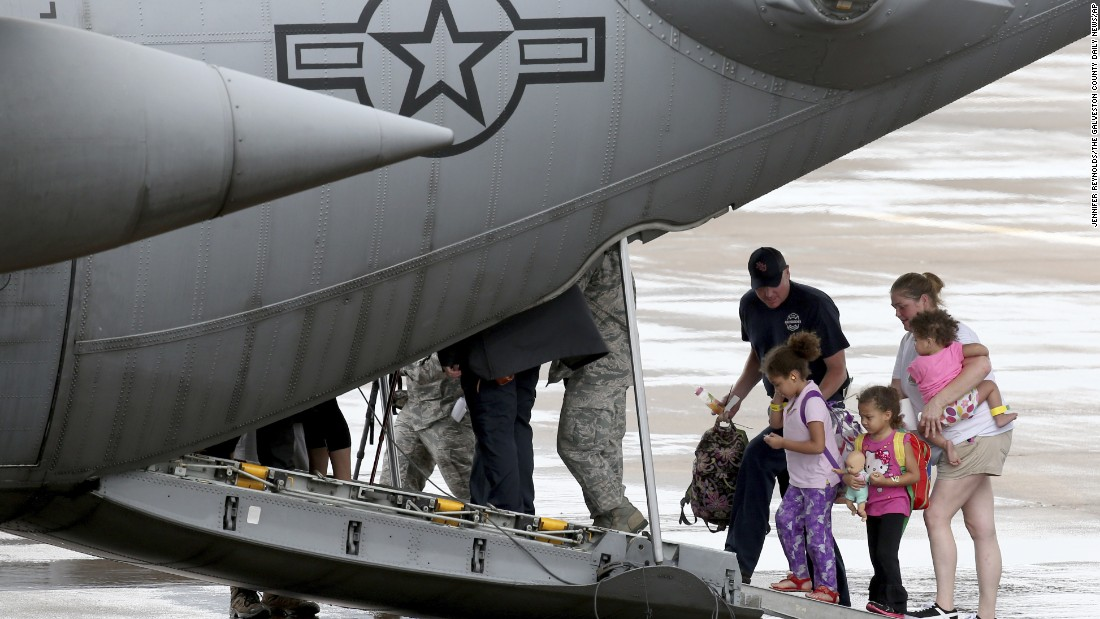 A firefighter helps Sara Golden and her daughters Paisley, Poppy and Piper board a Texas Air National Guard C-130 at Scholes International Airport in Galveston, Texas, on August 28.