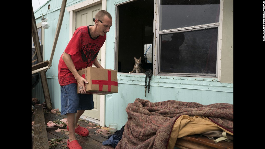 Sam Speights removes possessions from his damaged home in Rockport on August 28.