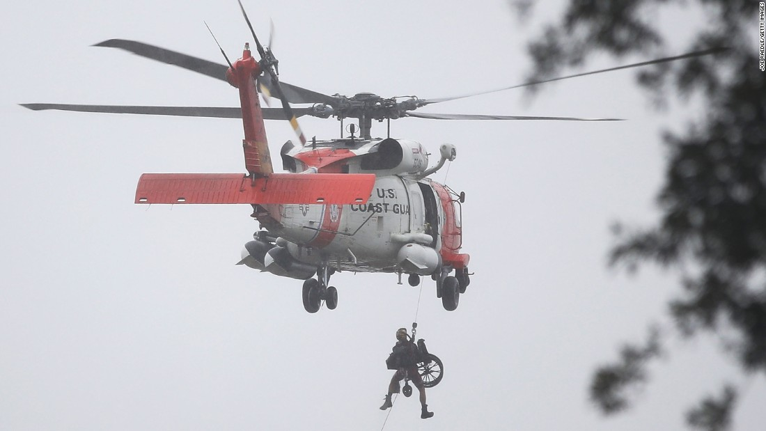 A Coast Guard helicopter hoists a wheelchair on board after lifting a person to safety from a flooded area of Houston on August 28.