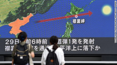 Pedestrians watch the news on a huge screen displaying a map of Japan (R) and the Korean Peninsula, in Tokyo on August 29, 2017, following a North Korean missile test that passed over Japan. Japanese Prime Minister Shinzo Abe said on August 29 that he and US President Donald Trump agreed to hike pressure on North Korea after it launched a ballistic missile over Japan, in Pyongyang's most serious provocation in years. / AFP PHOTO / Toshifumi KITAMURA        (Photo credit should read TOSHIFUMI KITAMURA/AFP/Getty Images)