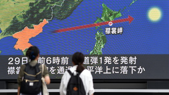Pedestrians watch the news on a huge screen displaying a map of Japan (R) and the Korean Peninsula, in Tokyo on August 29, 2017, following a North Korean missile test that passed over Japan. Japanese Prime Minister Shinzo Abe said on August 29 that he and US President Donald Trump agreed to hike pressure on North Korea after it launched a ballistic missile over Japan, in Pyongyang