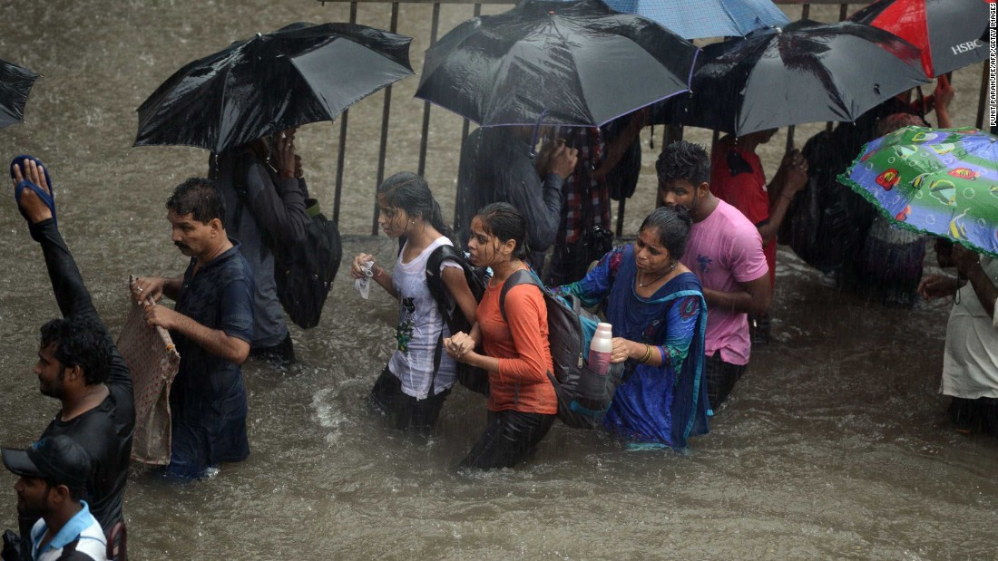 Heavy rain showers brought Mumbai to a standstill. Pedestrians had to walk through flooded streets, while dozens of flights and local train services were canceled.