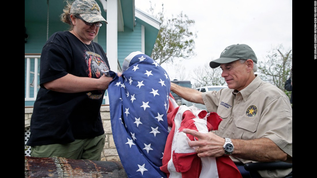 Bridget Brundrett presents an American flag to Texas Gov. Greg Abbott while  he was in