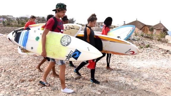 Students of the Rip Curl Surf Club Ngor surf school walk on the Almadie beach on May 23, 2015 in Dakar.