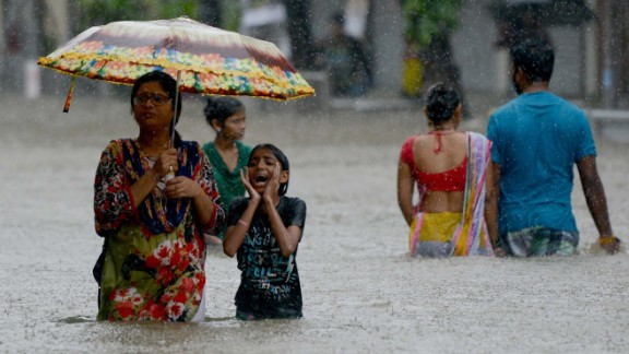 People wade through a flooded street during heavy rain showers in Mumbai on August 29, 2017.