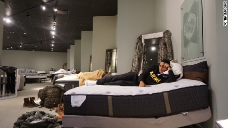 Aziz Shroff, 23, with the Texas National Guard, rests on a furniture store display mattress.