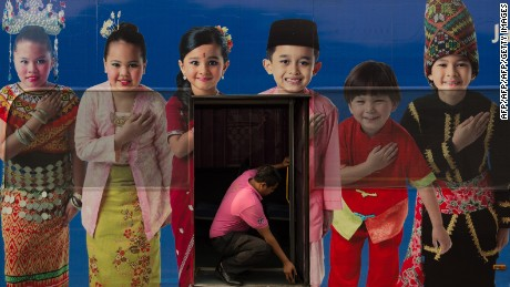 A man opens a bus door through an advertisement showing the Malaysia ethnic communities with traditional dress in Kuala Lumpur, September 25, 2013.