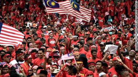 Pro-government ethnic Malay hardliners wave flags and shout slogans during a demonstration in Kuala Lumpur on September 16, 2015.