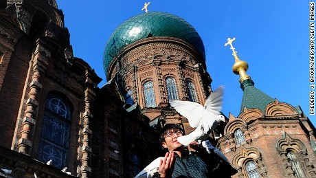 A man feeds pigeons beneath the onion dome rooftop of Saint Sophia Cathedral, a former Russian Orthodox church and one of the most famous landmarks in Harbin on March 16, 2011, in northeast China's Heilongjiang province. The cathedral was built in 1907 upon completion of the Trans-Siberian Railway in 1903, connecting Vladivostok with Lake Baikal via Manchuria, where the once small fishing village on the Songhua River, now Harbin, was developed by the Russians at the end of the 19th and beginning of the 20th centuries as the construction center for the railway. AFP PHOTO/Frederic J. BROWN (Photo credit should read FREDERIC J. BROWN/AFP/Getty Images)