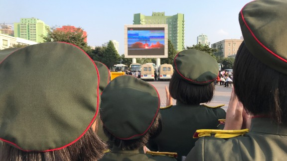 North Koreans watch news of the country's latest missile launch on an outdoor screen near Pyongyang's central railway station on August 30, 2017.