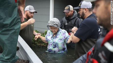 PORT ARTHUR, TX - AUGUST 30:  Volunteer rescuer workers help a woman from her home that was inundated with the flooding of Hurricane Harvey on August 30, 2017 in Port Arthur, Texas. Harvey, which made landfall north of Corpus Christi late Friday evening, is expected to dump upwards to 40 inches of rain in Texas over the next couple of days.  (Photo by Joe Raedle/Getty Images)