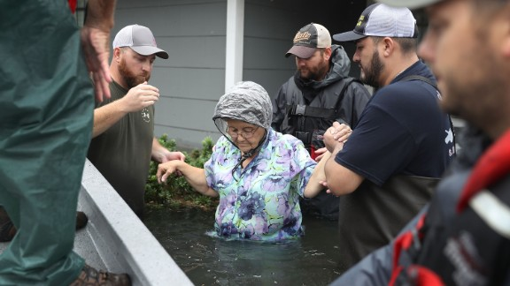 Volunteer rescue workers help a woman from her flooded home in Port Arthur, Texas.