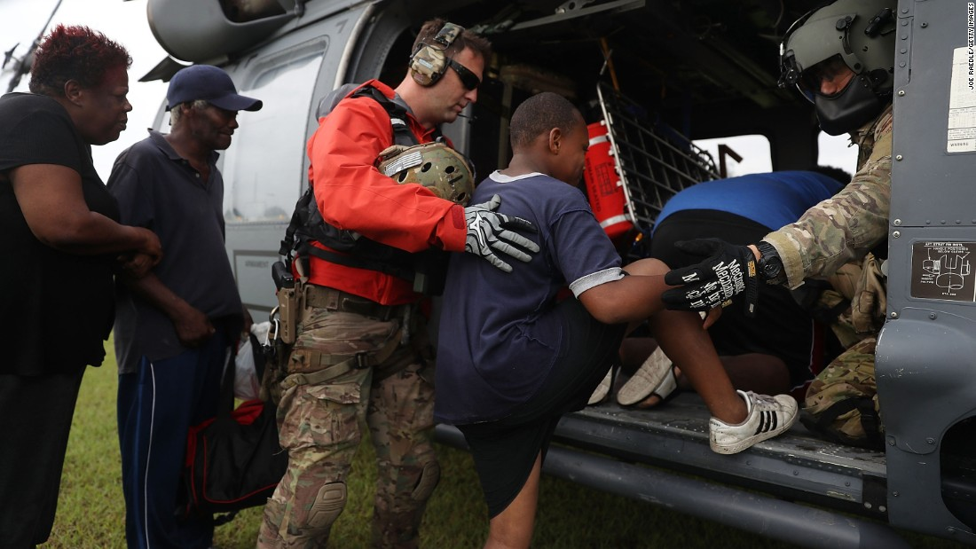 The Florida Air Force Reserve Pararescue team from the 308th Rescue Squadron helps evacuees board a helicopter in Port Arthur on August 30.