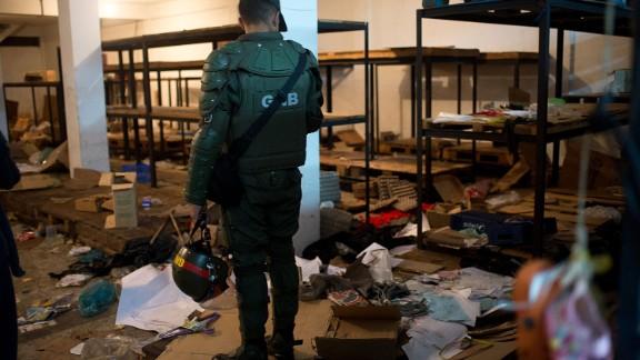 A member of the Venezuelan National Guard looks at the debris left in a looted supermarket in Ciudad Bolivar, Bolivar state, Venezuela, on December 19, 2016.