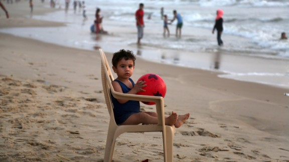 Palestinians swim in contaminated sea water at a beach near Gaza City in July.