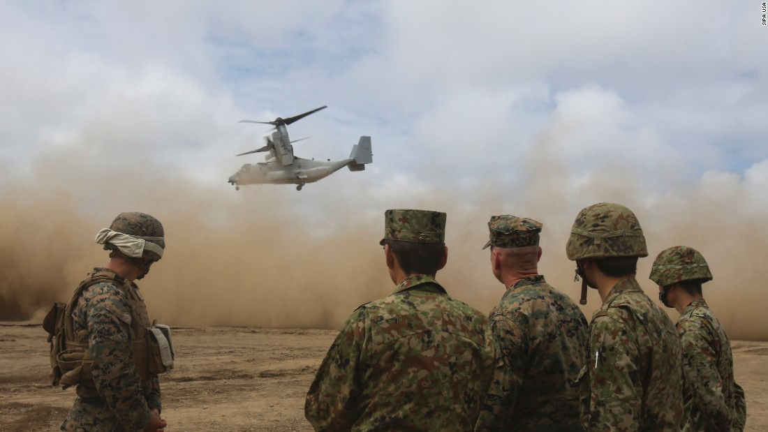 US Marines and Japanese troops watch an MV-22 Osprey take off during a joint training exercise in Hokudaien, Japan, on Friday, August 18.