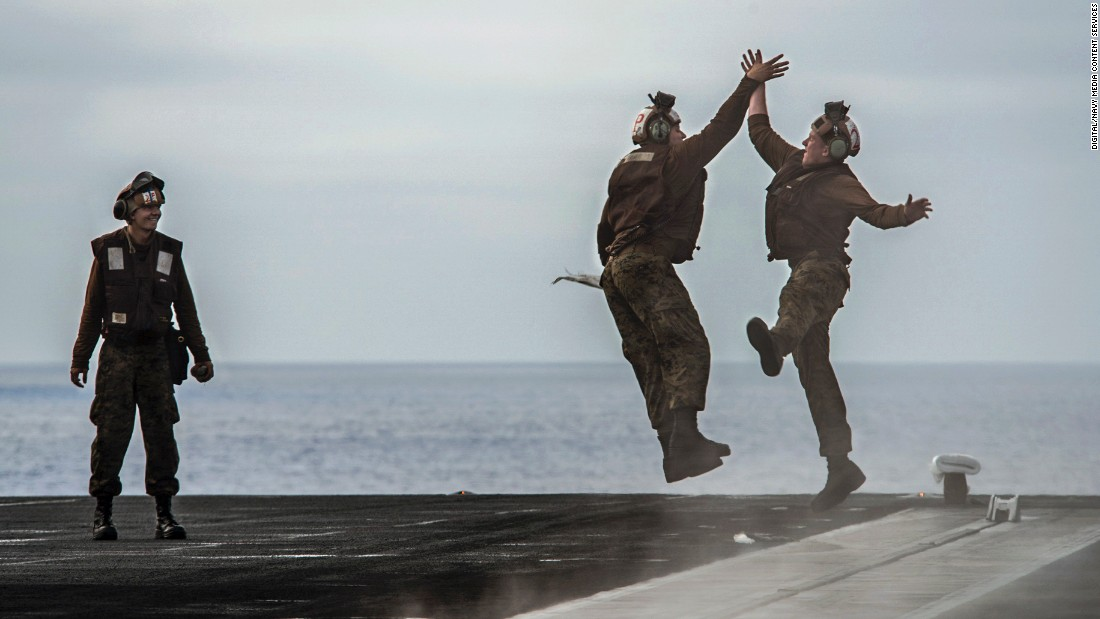 US Marines high-five each other after cleaning out pad eyes on the flight deck of the USS Theodore Roosevelt on Friday, August 4. The aircraft carrier was taking part in a training exercise in the Pacific Ocean.