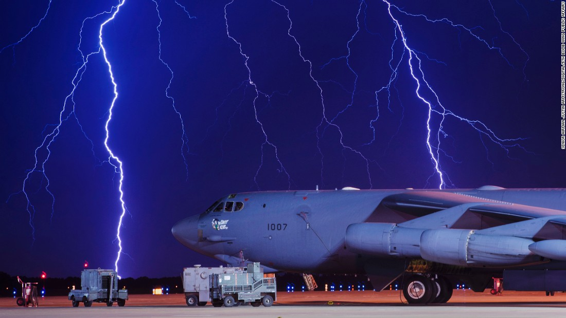 Lightning strikes behind a B-52 bomber at the Minot Air Force Base in North Dakota on Tuesday, August 8.