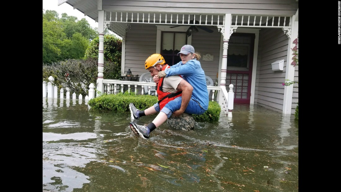 A Texas National Guardsman carries a Houston resident from her flooded home on Sunday, August 27.