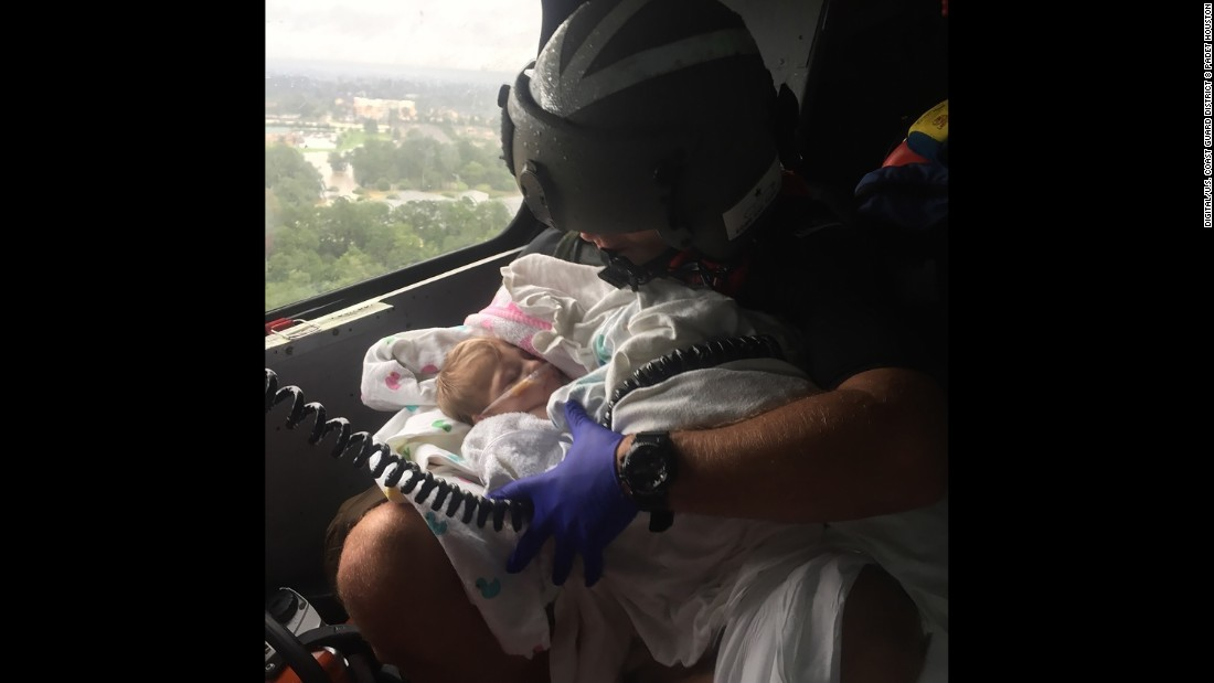 "A member of the US Coast Guard assists an infant over Houston on Tuesday, August 29. The city has been dealing with <a href=""http://www.cnn.com/2017/08/26/us/gallery/hurricane-harvey/index.html"" target=""_blank"">massive flooding</a> caused by Hurricane Harvey."
